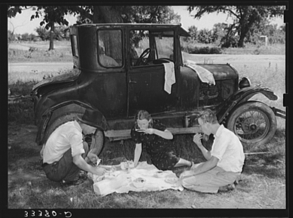 Migrant workers eating dinner by the side of their car while they are camped near Prague, Oklahoma. Lincoln County