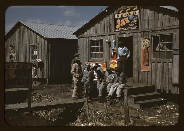 "Migratory laborers outside of a ""juke joint"" during a slack season, Belle Glade, Fla."