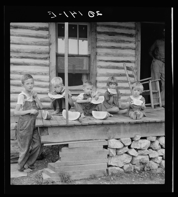 Millworker's children eating watermelon on porch of rented house. Six miles north of Roxboro, Person County, North Carolina