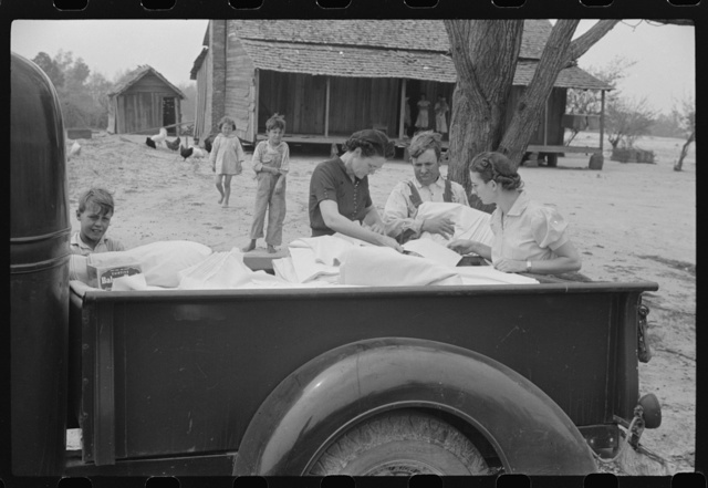 Miss Hesterley and Miss Christian, FSA (Farm Security Administration) home economists, delivering sheeting to Mr. Adkins, rural rehabilitation borrower. This is their first year on the program. There are nine in the family. Coffee County, Alabama