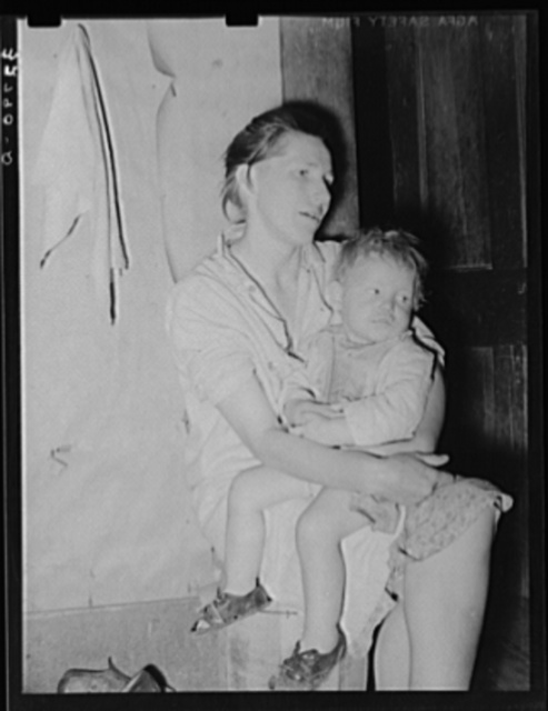 Mother and child. This woman, wife of an ex-farmer now living on relief, had pellagra in an advanced stage. She has had some treatment and shown great improvement but there were still evidences of mental disturbances. She was the mother of twelve children. The child in her arms has malaria as have probably the entire family. Jefferson, Texas