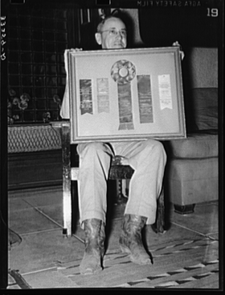 """Mr. Henry Fletcher, owner of the """"Walking X"""" Ranch, displaying awards won by his cattle. Marfa, Texas"""