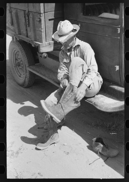 Mr. Johnson, FSA (Farm Security Administration) client with part interest in cooperative well, putting on his boots, near Syracuse, Kansas