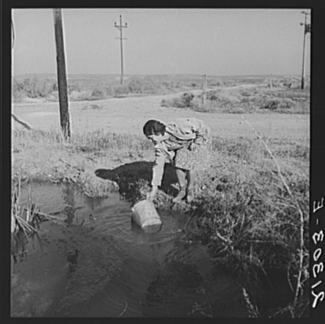 Mrs. Bartheloma dipping water from irrigation ditch for home use. Haul drinking water from town four miles over rough road. Nyssa Heights, Malheur County, Oregon