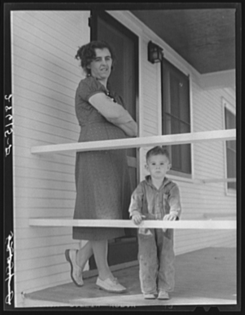 Mrs. Carl Higgins, wife of Mesa County, Colorado, tenant purchase borrower, and son on porch of their farmhouse