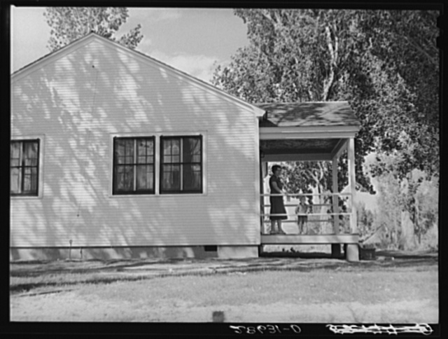 Mrs. Carl Higgins, wife of tenant purchaser, and son on porch of home. Mesa County, Colorado
