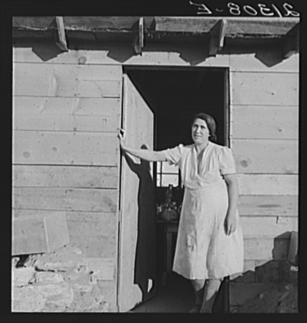 Mrs. Dougherty in doorway of basement house. Warm Springs, Malheur County, Oregon