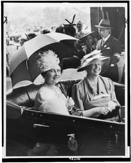 [Mrs. Eleanor Roosevelt and Queen Elizabeth, holding umbrella, in automobile, leaving station for the White House]