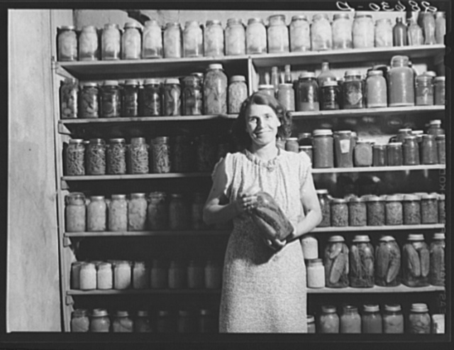 Mrs. H.H. Poland, wife of rehabilitation client, with preserved food. Mesa County, Colorado