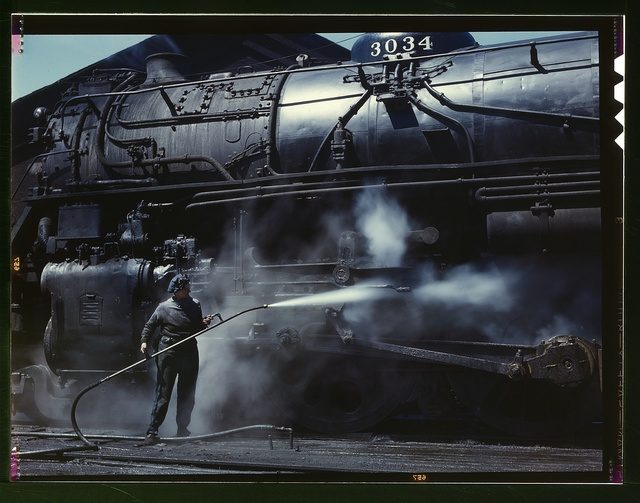 """Mrs. Viola Sievers, one of the wipers at the roundhouse giving a giant """"H"""" class locomotive a bath of live steam, Clinton, Iowa. Mrs. Sievers is the sole support of her mother and has a son-in-law in the Army"""