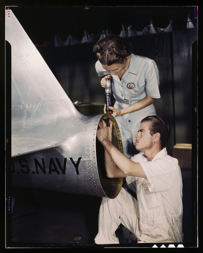 Mrs. Virginia Davis, a riveter in the assembly and repair department of the Naval Air Base, supervises Chas. Potter, a NYA trainee from Michigan; Corpus Christi, Texas