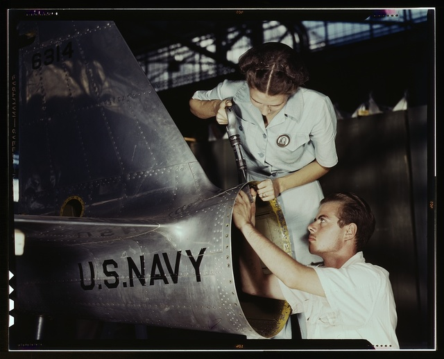 Mrs. Virginia Davis, a riveter in the assembly and repair department of the Naval air base, supervises Chas. Potter, a NYA trainee from Michigan, Corpus Christi, Texas. After eight weeks of training he will go into civil service. Should he be inducted or enlist in the armed service, he will be valuable to mechanized units of the Army or Navy