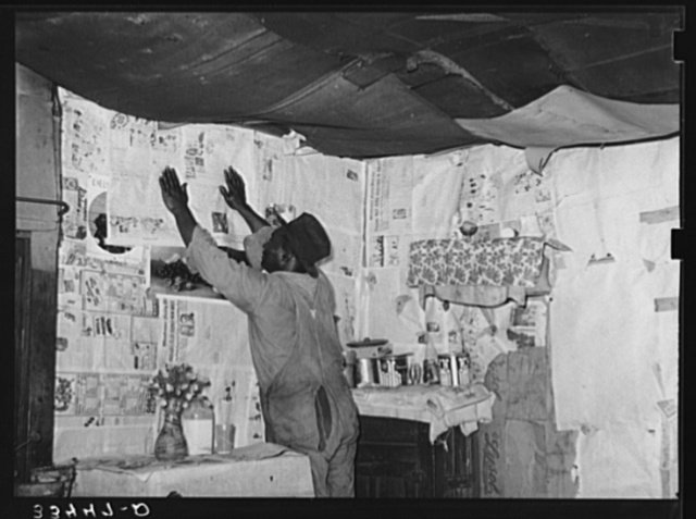 Negro day laborer repapering his house. The wall and roof is in such bad condition that the house must be repapered every rain. Muskogee, Oklahoma