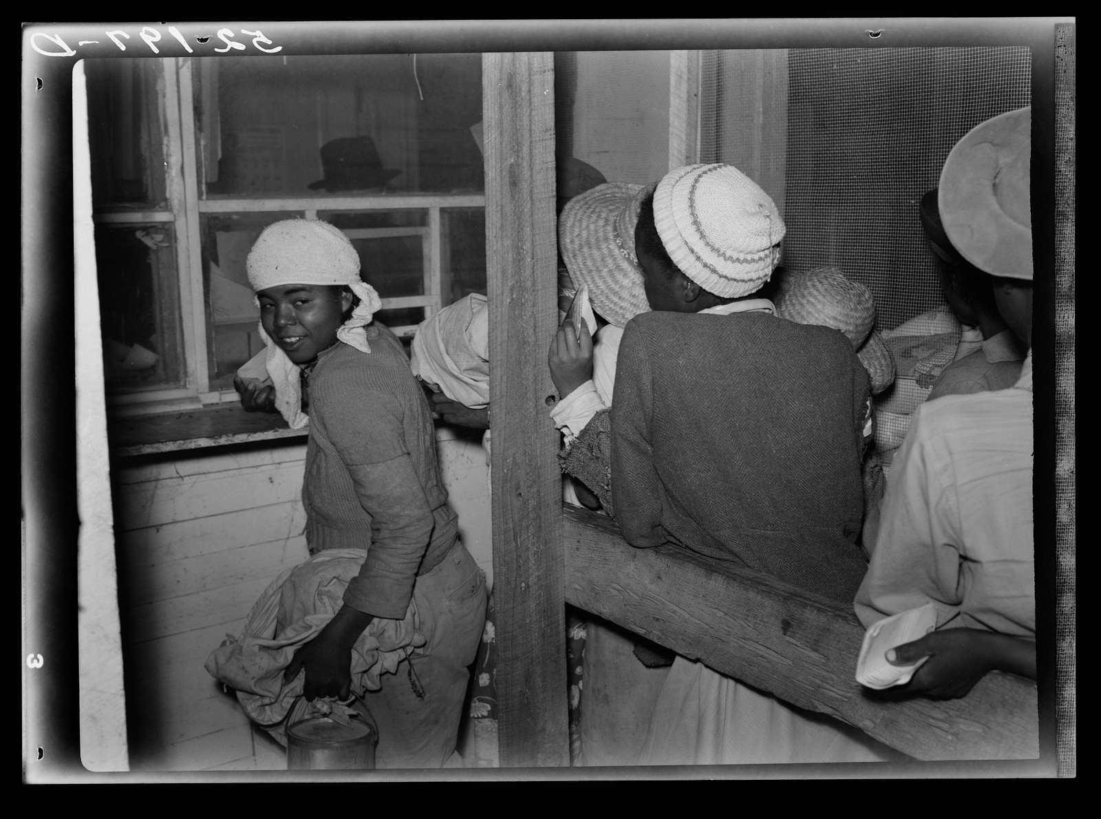 Negro day laborers brought in truck from nearby towns, waiting to be paid off for cotton picking and buy supplies inside plantation store on Friday night. Marcella Plantation. Mississippi Delta. Mississippi