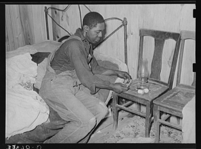 Negro man lighting lamp in bedroom of his home near Hammond, Louisiana. He works for a strawberry grower, doing odd jobs about the place