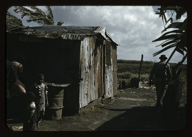 Negro migratory workers by a shack, Belle Glade, Fla.