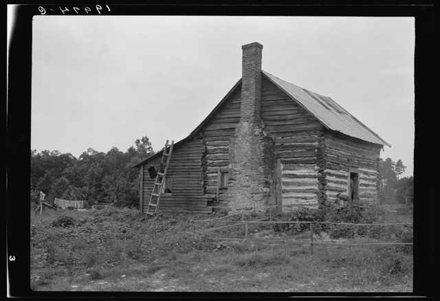 Negro sharecropper house. Note chimney leanto with kitchen stove pipe stuffed through side of wall and cap off with joint of tobacco flue to keep smoke from blowing back into house. Note also flower garden protected by slender fence of lathes. Person County, North Carolina
