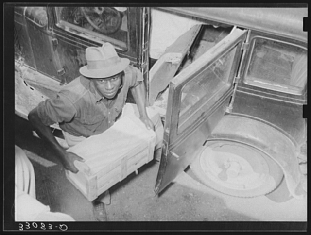 Negro unloading crate of strawberries at loading point. Hammond, Louisiana