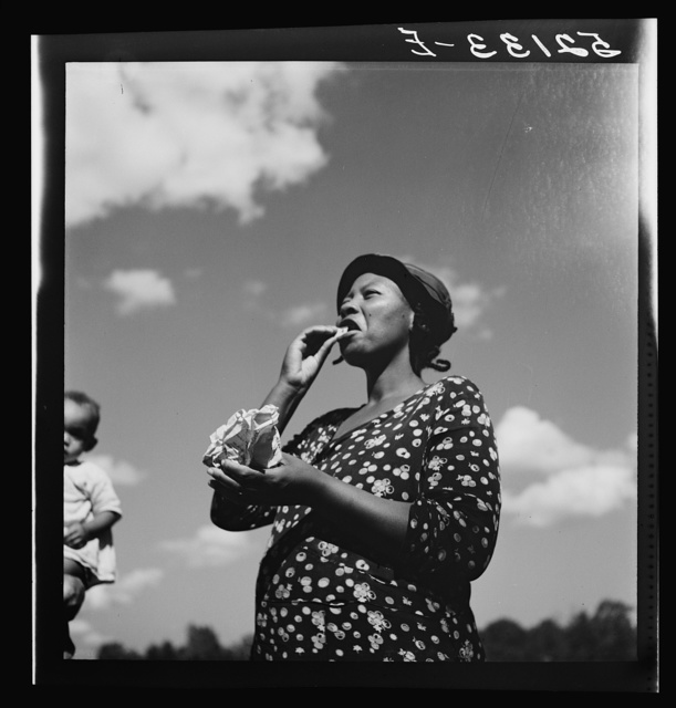 Negro woman dipping snuff while watching them make sorghum syrup at Cane Mill, on Wes Chris' property near Carr, Orange County, North Carolina. See general notes on subregion, September 28, 1939