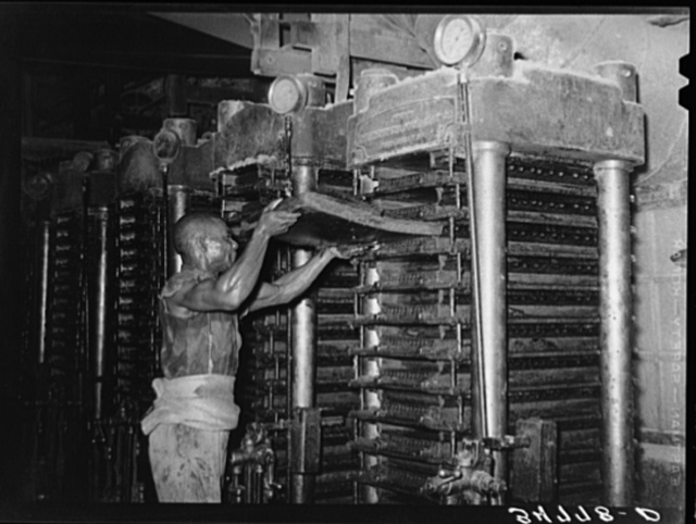 Negro workman inserting cotton seed filled mat into hydraulic press which will press out the oil and leave the cake. Cotton seed oil mill. McLennan County, Texas