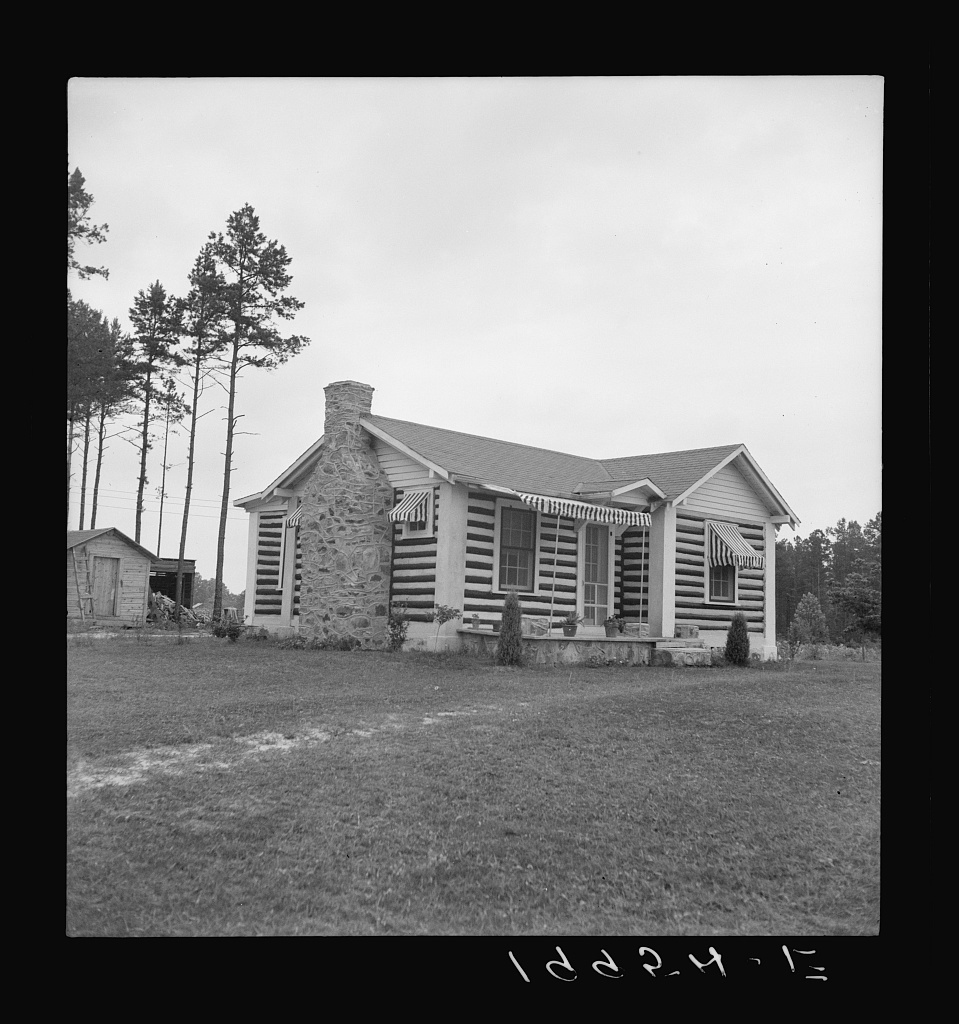 Note on architecture. A new very fancy log bungalow showing influence of tobacco barn construction. Logs are painted black and white. Near Gordonton, North Carolina