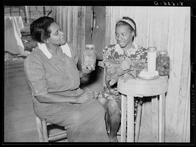Nurse Shamburg gives Viola Pettway instructions and help about her diet in treatment of pellagra. She has been sick about four years and is a little better now. Her mother has thirteen children and twenty-five dollars a month for all. Table top is made from cheese box. Gee's Bend, Alabama