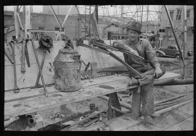 Oil field worker resting on pipe wrench, Kilgore, Texas
