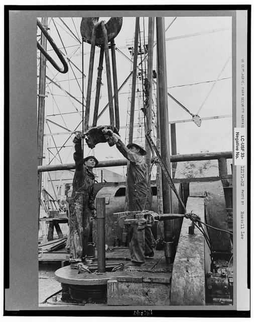 Oil field workers, reaching for clamp on elevator. The elevator removes the pipe from the drill hole, Kilgore, Texas
