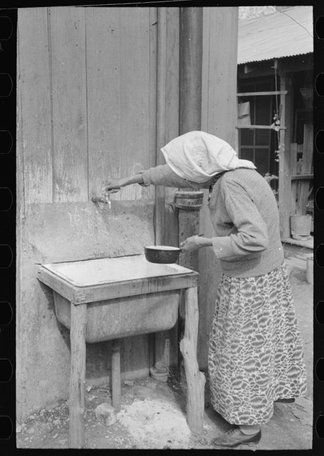 Old Mexican woman drawing water from community hydrant, San Antonio, Texas