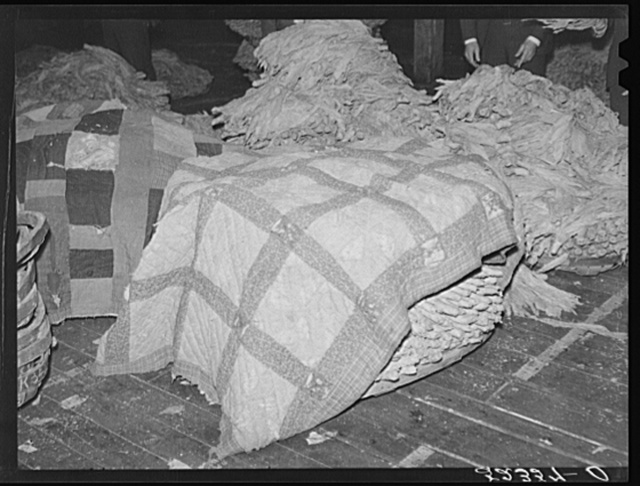 "Old quilts and sacks are used to keep tobacco moist and ""in order"" while waiting for auction sale in warehouse. Durham, North Carolina"