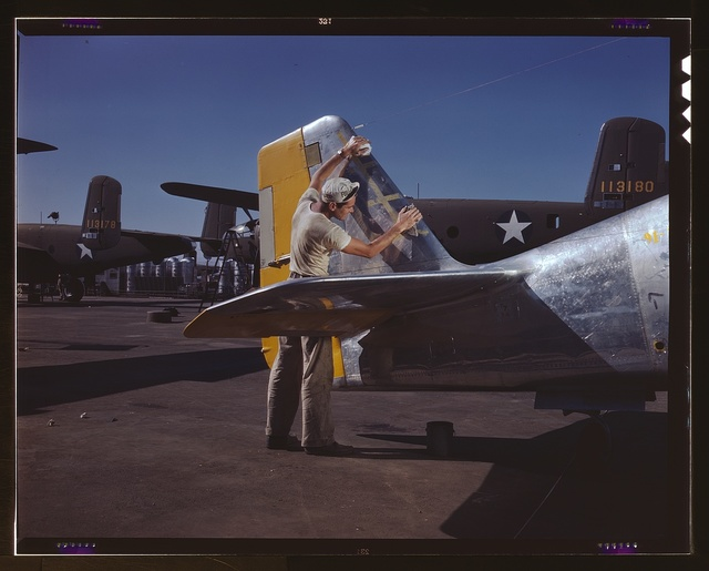 On North American's outdoor assembly line, a painter cleans the tail section of a P-51 fighter prior to spraying the olive-drab camouflage of the U.S. Army, N[orth] A[merican] Aviation, Inc., Inglewood, Calif.