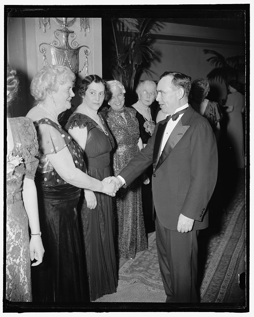 One republican greets another. Washington, D.C., March 27. Mrs. Edward Everett, Dolly Gann, sister of the late Vice President Curtis and president of the League of Republican Women of the District of Columbia, enthusiastically shook hands with Minority Leader of the House, Rep. Joe Martin of New York when he came to the receiving line at the League's dinner tonight. Rep. Martin has proved himself a threat to the democratic bloc in the House because of his tight organization. Mrs. Robert Taft, wife of the Ohio senator is next to Mrs. Gann. 3-27-39