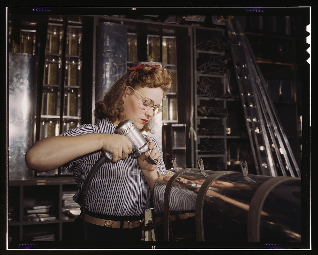 Operating a hand drill at North American Aviation, Inc., [a] woman is working in the control surface department assembling a section of the leading edge for the horizontal stabilizer of a plane, Inglewood, Calif.