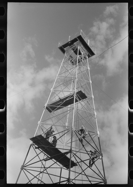 Painting a derrick, Seminole oil field, Oklahoma. Notice lack of safety belts. Painters say that safety devices slow them down too much