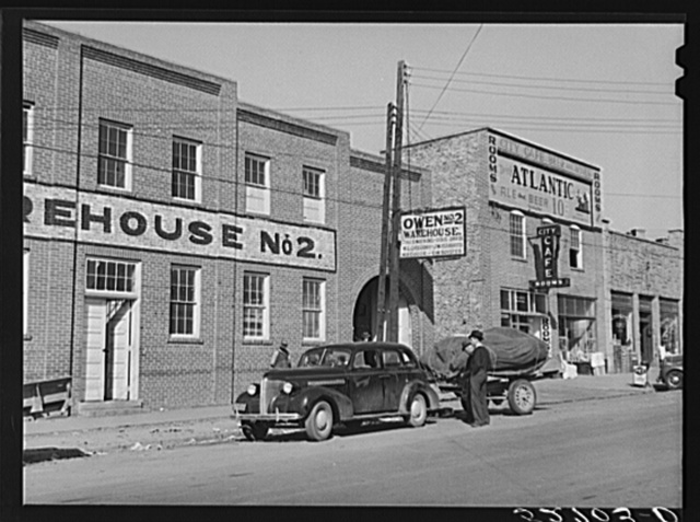Part of tobacco warehouse showing farmer's car with trailer of tobacco for auction. Oxford, North Carolina