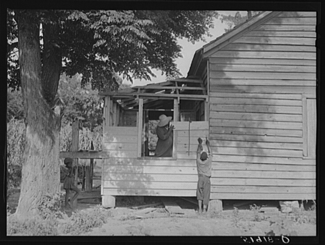 Pauline Clyburn, rehabilitation client, Manning, Clarendon County, South Carolina, and her son repairing home