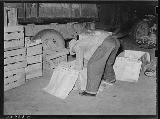 Peddler lining crates with newspapers before packing them with vegetables. San Antonio, Texas