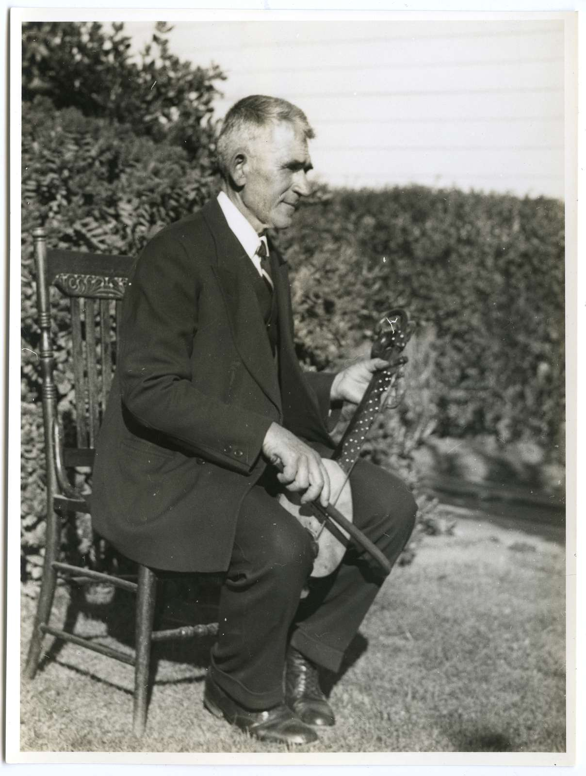 Peter Boro playing gusle, seated, right profile, portrait, photograph