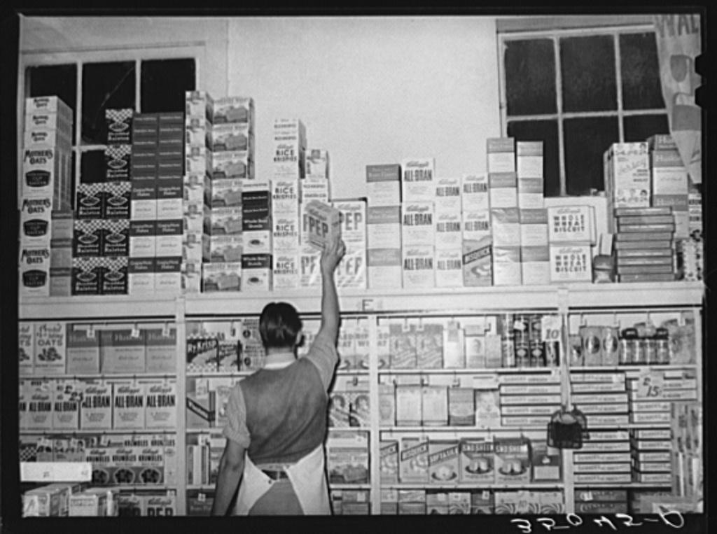 Placing packaged goods on display rack. Retail grocery, San Angelo, Texas