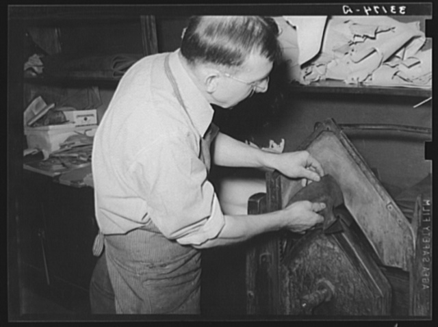 Placing pieces of leather into crimping machine to shape the lowers of the boots. Boot shop, Alpine, Texas