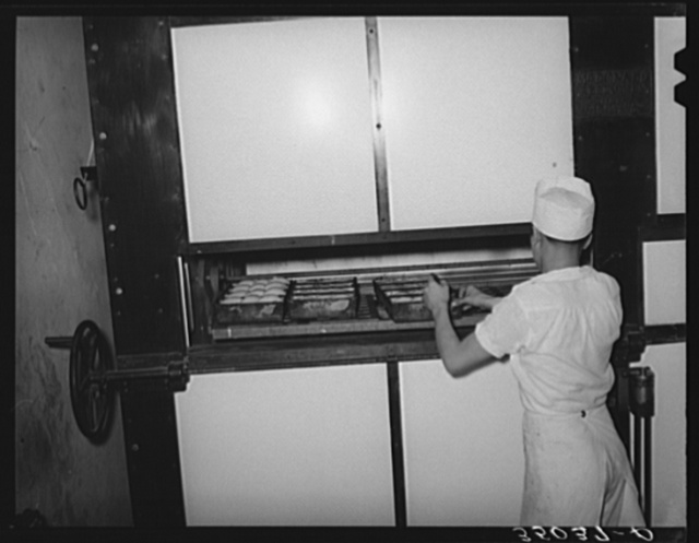 Placing rolls in reel oven to be baked. Bakery, San Angelo, Texas