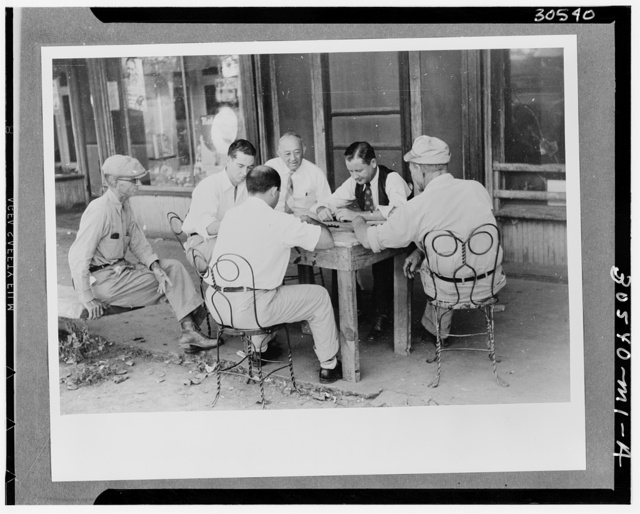 Playing dominoes or cards in front of drug store in center of town in Mississippi Delta, Mississippi