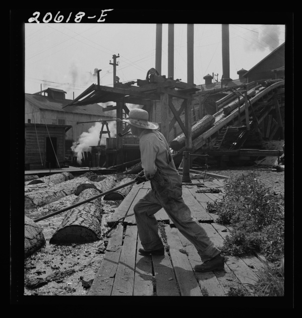 """""""Pond monkey"""" guides course of logs from the mill pond to the chute. Pelican Bay Lumber Company mill. Klamath Falls, Oregon"""