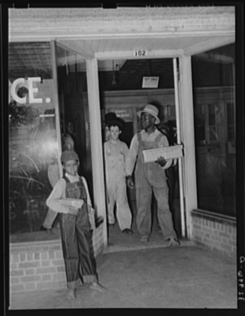 Post office. Negro coming out of door with carton of baby chicks. San Augustine, Texas