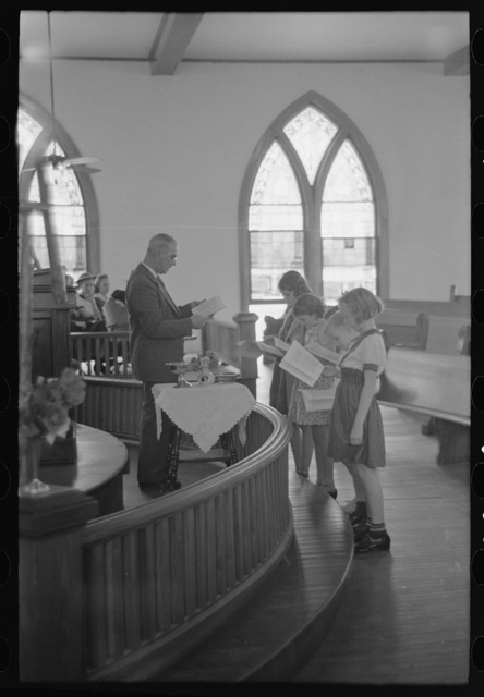 Preacher reading the lesson and instructions before baptism, San Augustine, Texas