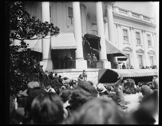 PRESIDENT AND FIRST LADY GREET EGG ROLLERS. WASHINGTON, D.C. APRIL 10. PRESIDENT AND MRS. ROOSEVELT WAVE A GREETING TO THE THOUSANDS OF YOUNGSTERS WHO GATHERED ON THE WHITE HOUSE LAWN TODAY TO ROLL THEIR GAYLY COLORED EASTER EGGS