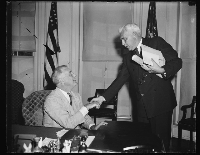 PRESIDENT ROOSEVELT GREETS McNUTT. WASHINGTON, D.C. AUGUST 1. PRESIDENT ROOSEVELT GREETS PAUL V. McNUTT, FORMER GOVERNOR GENERAL OF THE PHILIPPINES AND NEW FEDERAL SECURITY ADMINISTRATOR, UPON HIS ARRIVAL AT THE WHITE HOUSE TODAY TO PRESENT A SET OF FLAGS MADE BY PHILIPPINE RESIDENTS. THE FLAGS, ALL MADE BY HAND, WERE GIVEN AS A TOKEN OF GOODWILL FROM THE PHILIPPINES TO THE UNITED STATES. THE PRESIDENT INDICATED THE FLAGS WOULD BE PLACED IN THE NEW LIBRARY AND ARCHIVES BUILDING NOW UNDER CONSTRUCTION AT HIS HOME IN HYDE PARK