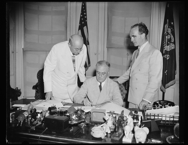 PRESIDENT SIGNS NEW COURT BILL. WASHINGTON, D.C. AUGUST 7. PRESIDENT ROOSEVELT TODAY SIGNED A BILL TO ESTABLISH A NEW ORGANIZATION FOR HANDLING THE ADMINISTRATION OF U.S. COURTS. UNDER THE MEASURE, INTRODUCED BY SENATOR ASHURST OF ARIZONA, CONTROL OF PERSONNEL WILL BE PLACED UNDER A DIRECTOR WHO WILL BE HEAD OF 'THE ADMINISTRATIVE OFFICES OF THE UNITED STATES COURTS.' THIS DIRECTOR, APPOINTED BY THE SUPREME COURT, WILL RECEIVE $10,000 YEARLY AND WILL HAVE AN ASSISTANT TO RECEIVE $7,500. L TO R: HOMER S. CUMMINGS, FORMER ATTORNEY GENERAL; PRESIDENT ROOSEVELT; AND ATTORNEY GENERAL FRANK MURPHY