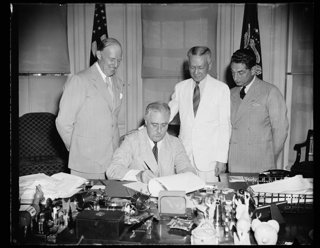 PRESIDENT SIGNS PHILIPPINE BILL. WASHINGTON, D.C. AUGUST 7. PRESIDENT ROOSEVELT TODAY SIGNED A MEASURE DESIGNED TO FACILITATE THE ECONOMIC ADJUSTMENT OF THE PHILIPPINE COMMONWEALTH TO INDEPENDENCE STATUS. IT PROVIDES FOR GRADUALLY DECLINING DUTY-FREE QUOTAS ON IMPORTS FROM THE PHILIPPINES OF COCONUT OIL, CIGARS, AND PEARL BUTTONS. THE QUOTAS DECREASE BY 5 PER CENT EVERY YEAR UNTIL 1946, WHEN FULL POLITICAL INDEPENDENCE IS GRANTED THE ISLANDS. L TO R: FRANCIS B. SAYRE, NEW PHILIPPINE GOVERNOR; PRESIDENT ROOSEVELT; SERGIO OSMENA, VICE PRESIDENT OF THE PHILIPPINES; AND J.M. ELIZALDE, RESIDENT PHILIPPINE COMMISSIONER