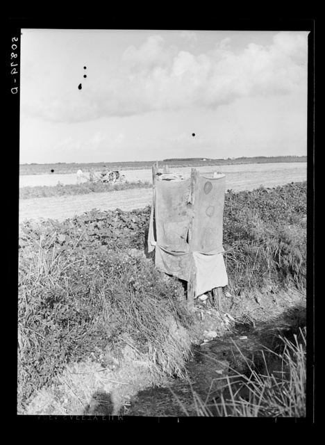 Privy alongside irrigation and drainage ditch for agricultural workers. Homestead, Florida
